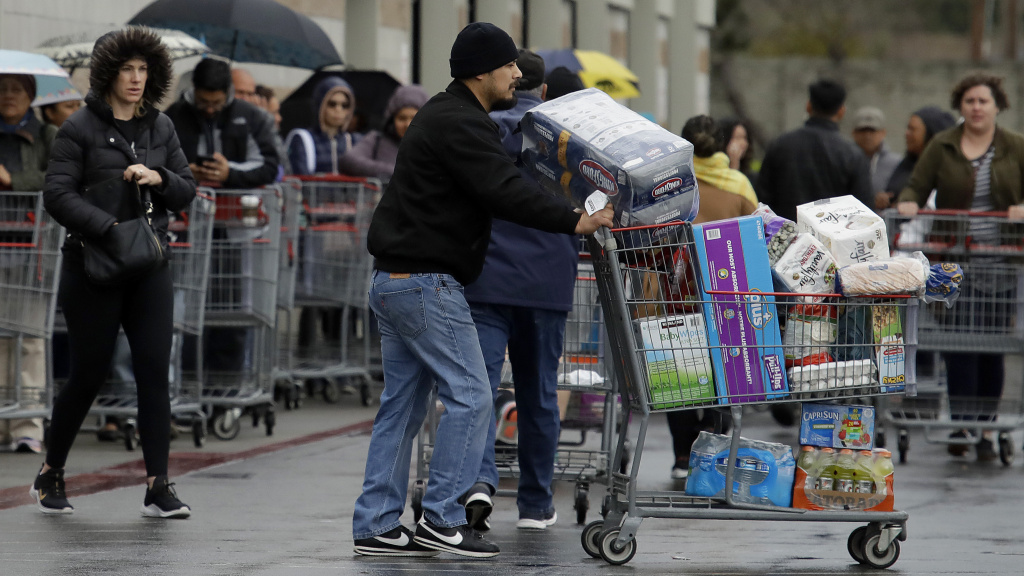 Costco customers roll groceries to their cars as others wait to enter the store on Saturday, March 14, 2020, in San Leandro, Calif.