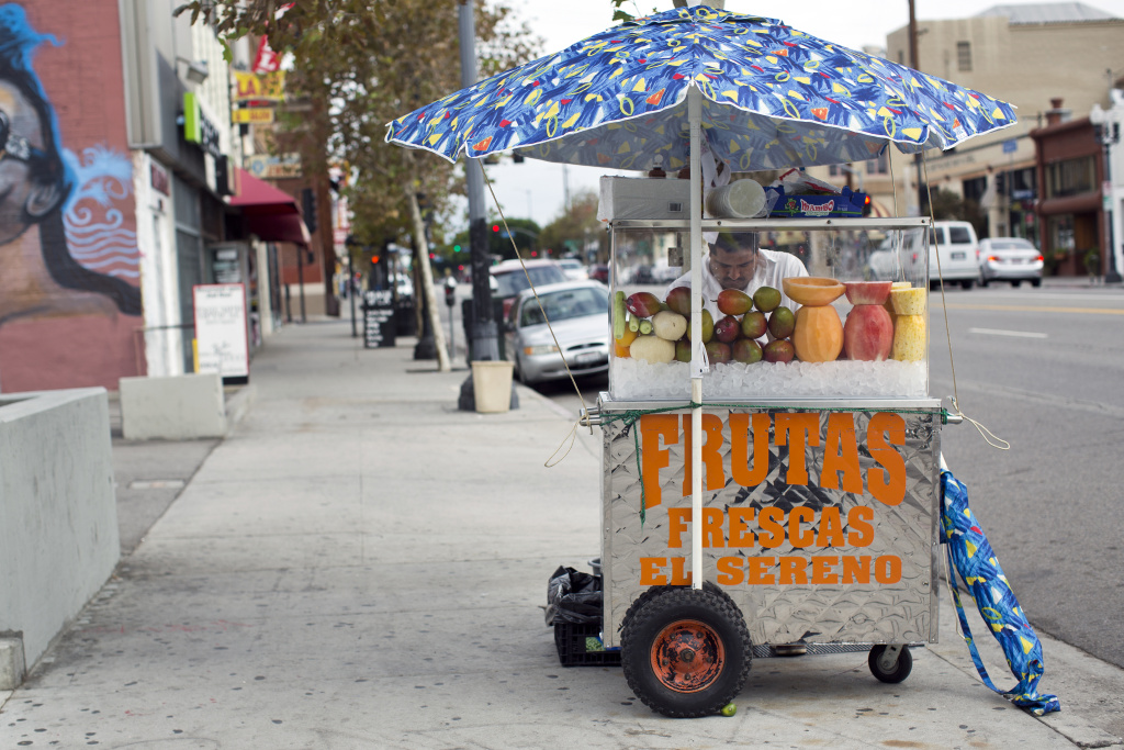 FILE PHOTO: A street vendor sells fruit in Los Angeles' Highland Park neighborhood.