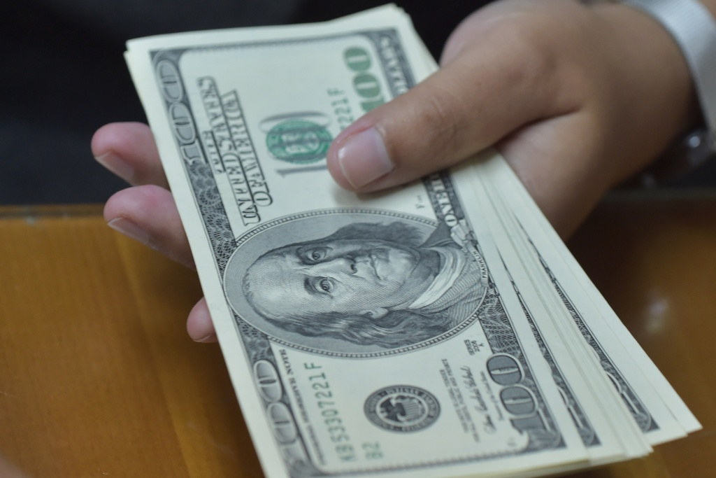 An employee holds US dollar banknotes at an Indonesian money changer's office in Jakarta on August 27, 2015.