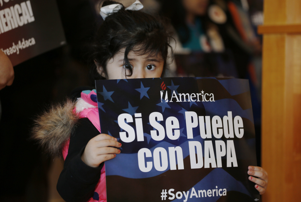 File photo: Three-year-old Genesis Moreno Betancurth, of Denver, holds a placard during a news conference in the Denver Public Library, Tuesday, Feb. 17, 2015, in Denver. The White House promised an appeal after a federal judge in Texas temporarily blocked President Barack Obama's executive action on immigration and gave a coalition of 26 states time to pursue a lawsuit aiming to permanently stop the orders.