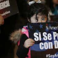 Three-year-old Genesis Moreno Betancurth, of Denver, holds a placard during a news conference in the Denver Public Library, Tuesday, Feb. 17, 2015, in Denver. The White House promised an appeal Tuesday after a federal judge in Texas temporarily blocked President Barack Obama's executive action on immigration and gave a coalition of 26 states time to pursue a lawsuit aiming to permanently stop the orders. (AP Photo/David Zalubowski)