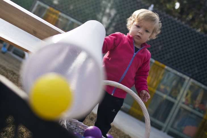 Clara, a student in the six to 18-month-old class at Caltech's Children's Center, plays by dropping balls down a tube on Wednesday morning, Jan. 21. The school has made engineering a focus in curriculum.