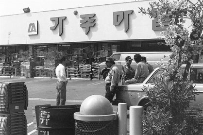 Korean Americans are standing in front of a barricaded Korean supermarket during the LA Riots.