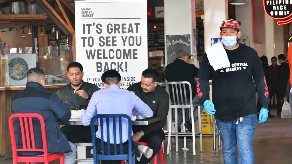 People enjoy lunch at Grand Central Market as indoor dining reopens in Los Angeles on March 15. The U.S. economy expanded at a rapid pace in the first three months of the year and is expected to grow at its fastest rate since 1984.