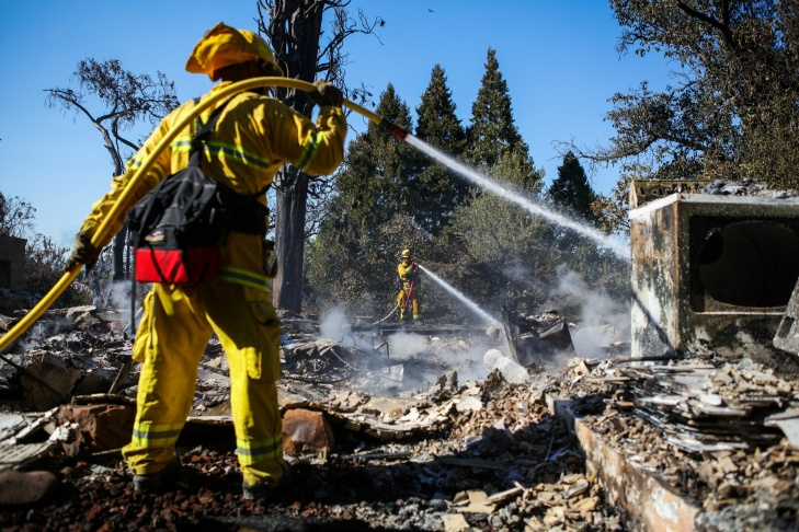 A firefighter works to contain embers on the remains of a house destroyed in the Clayton Fire are seen in Lower Lake, California, August 15th, 2016.