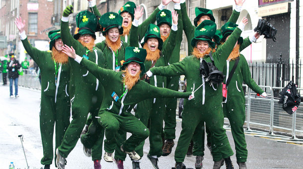 Parade-goers dressed as leprechauns jump up and shout as they prepare to attend St. Patrick's Day festivities in Dublin.