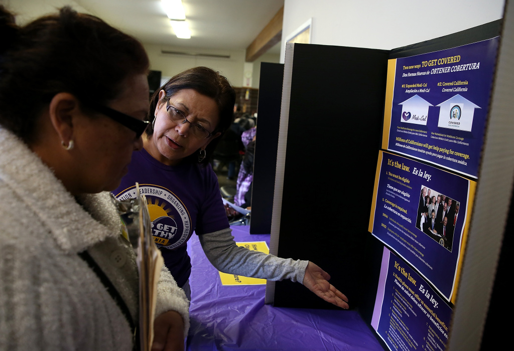 A worker explains the process for registering during a healthcare enrollment fair at the Bay Area Rescue Mission on March 31, 2014 in Richmond, California. More than 1.2 million people signed up for health plans through the state's health insurance exchange by the March 31 deadline.