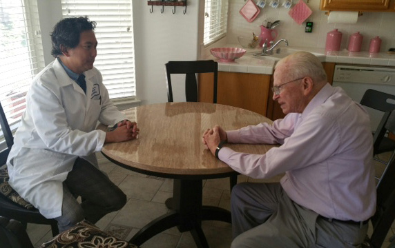 Dr. Earl Quijada of Kaiser Permanente visits with John Stanton in the kitchen of his home in Hemet.
