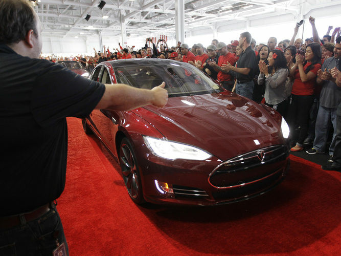 Tesla workers cheer on one the first Tesla Model S cars sold during a rally at the Tesla factory in Fremont, Calif., in June. The company is now unveiling a new network of refueling stations for the vehicles.