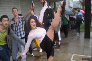 Jamie Goodwin kicks high as Robert Roldan and Adrian Lee wait in line to audition to dance on the Academy Awards show.