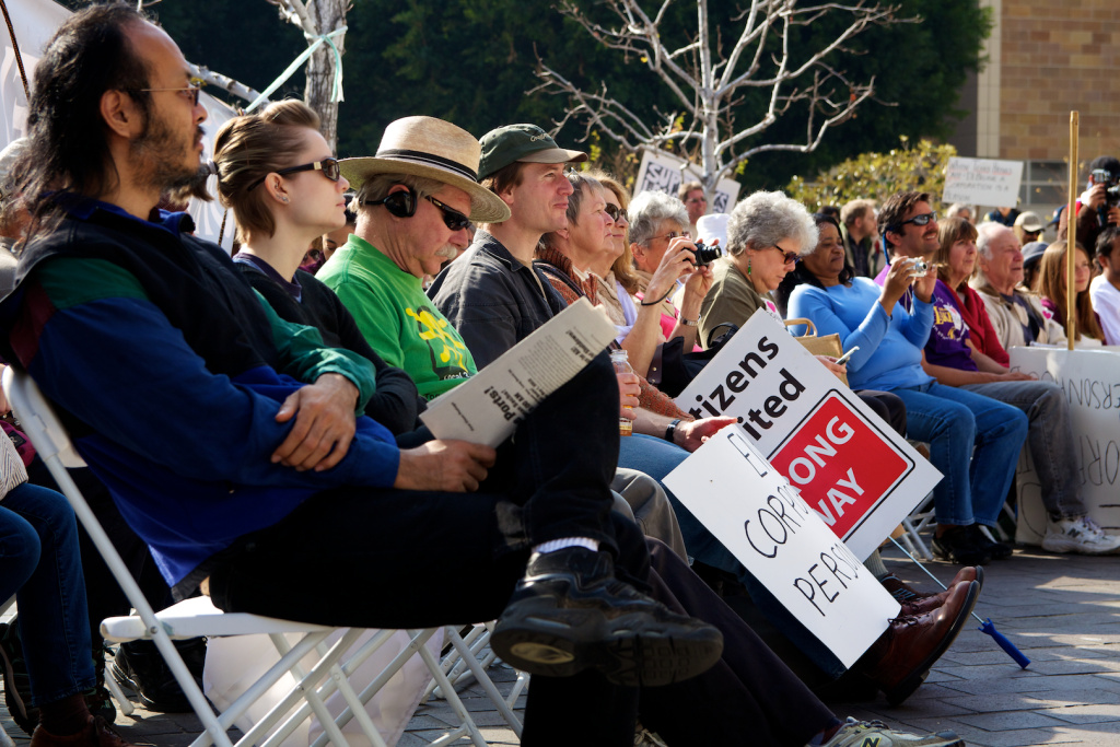 File photo: Several people listen to a speaker express her opposition to the Citizens United ruling at an Occupy Courts protest in Los Angeles in 2012.