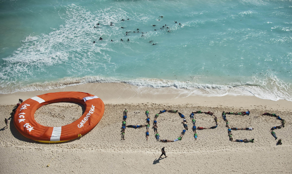 Members of Greenpeace make a performance using a giant inflatable life ring, in a beach of Cancun Mexico, on December 10, 2010 during the COP16 United Nations Climate Change conference.