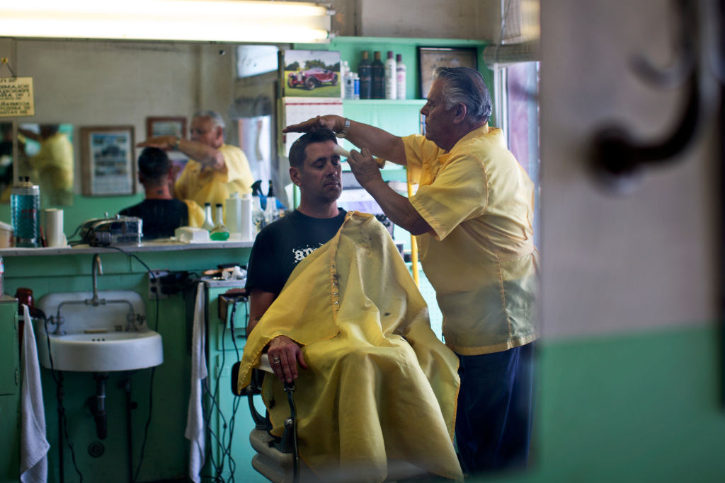 Enrique Banuelos cuts Phil Jahnke's hair at the barbershop he opened four decades ago on Olympic Boulevard in the Pico neighborhood.