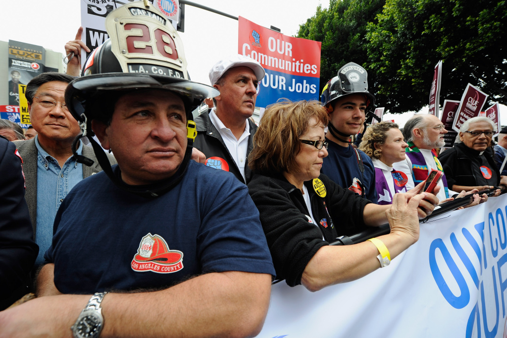 David Lopez, (L) a Los Angeles County Firefighter, Maria Elena Durazo, (C) from Los Angeles County Federation of Labor, AFL-CIO, participate in a march supporting union workers in what protesters have dubbed,