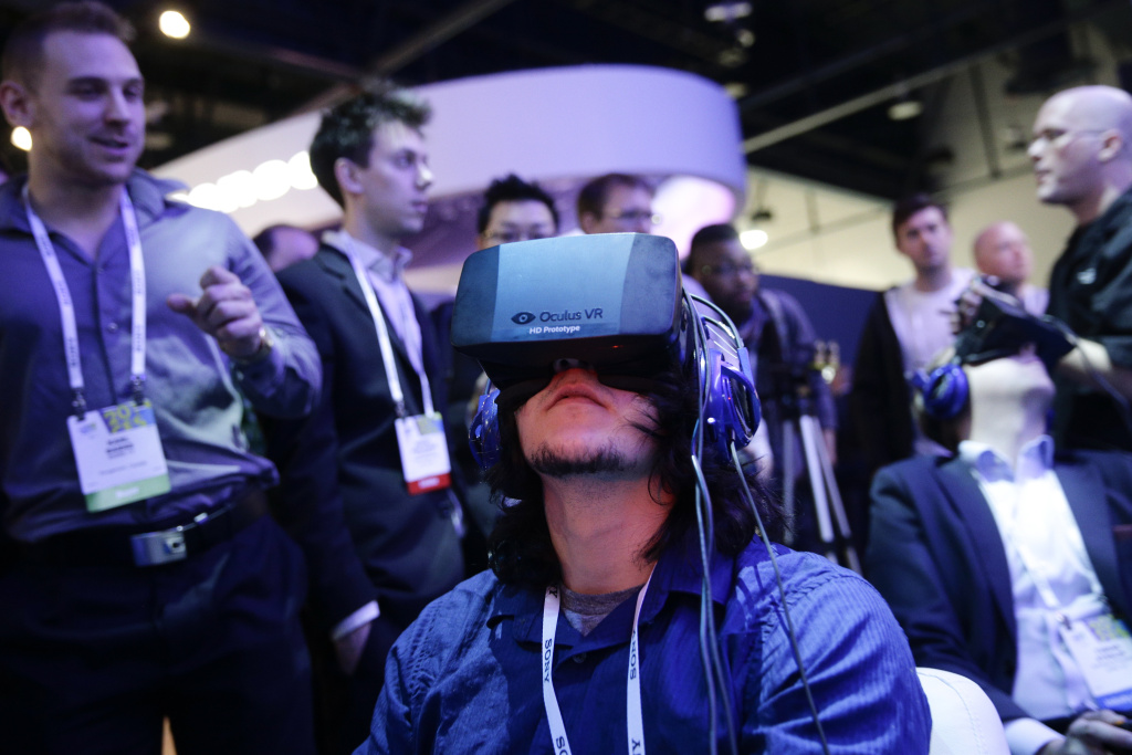 In this Jan. 7, 2014 file photo, show attendees play a video game wearing  Oculus Rift virtual reality headsets at the Intel booth at the International Consumer Electronics Show(CES), in Las Vegas. Many backers who helped it raise more than $2.4 million through Kickstarter in 2012 were shocked last week when Oculus announced it was selling itself to social media company Facebook for $2 billion.