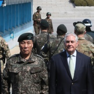 US Secretary of State Rex Tillerson (C) poses for a photograph with US Gen. Vincent K. Brooks (R), commander of the United Nations Command, Combined Forces Command and United States Forces Korea, and deputy Commander of the Combined Force Command General Leem Ho-young (L) as two North Korean soldiers (top) look on at the border village of Panmunjom, which has separated the two Koreas since the Korean War, on March 17, 2017.