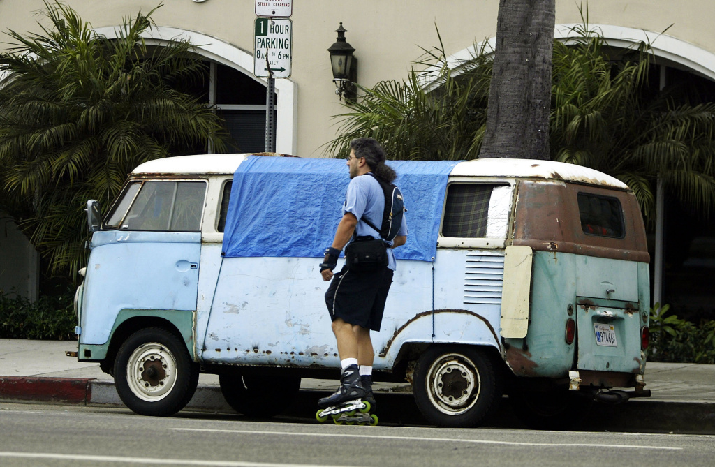 A skater passes a van where a homeless person is sleeping July 13, 2004 in Venice, California.