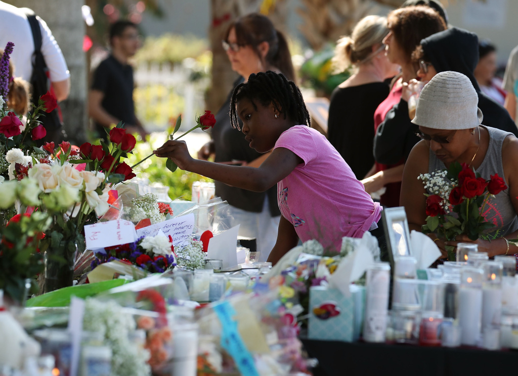 People bring flowers to a temporary memorial at Pine Trails Park on February 17, 2018 in Parkland, Florida.