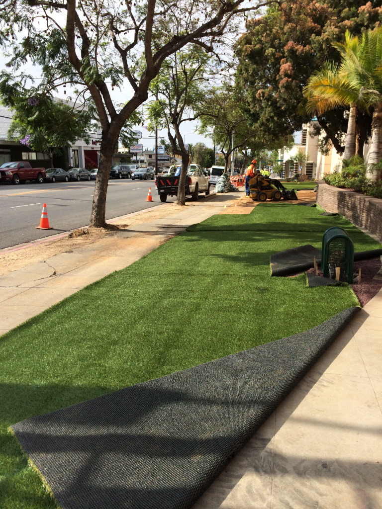 Workers install fake grass as part of a drought-tolerant lawn at the Los Angeles Department of Water and Power building in Los Feliz.