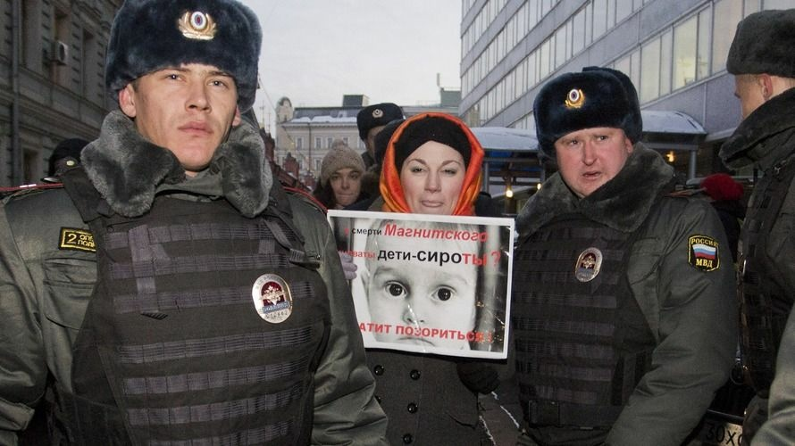 Police officers detain a protester outside the lower house of Russia's parliament on Wednesday. Russian president Vladimir Putin has approved a bill banning Americans from adopting Russian children after the U.S. passed a law that rebukes Russia for human rights abuses.