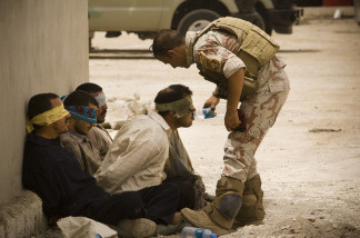An Iraqi soldier from 2nd Division gives water to detainees after returning to their base from a morning mission on June 5 , 2010 in Mosul, Iraq.