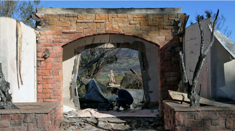 Jason Meek sifts through the remains of his home in Sonoma County.