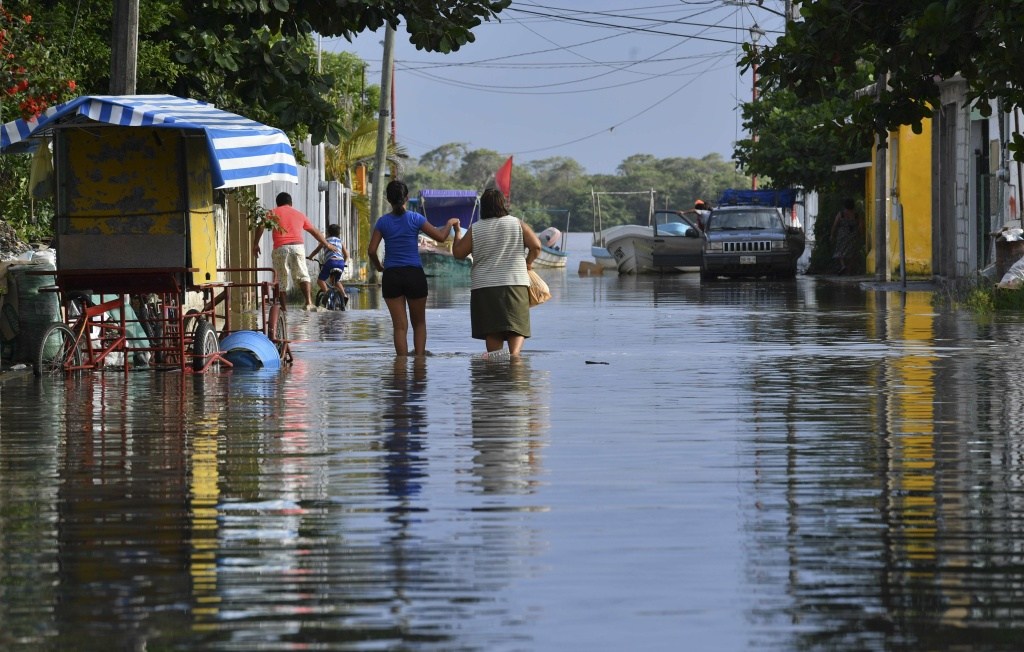 Residents walk on a street flooded by the Tecolutla River a day after Hurricane Katia passed through Tecolutla, Veracruz state, Mexico on September 9, 2017.