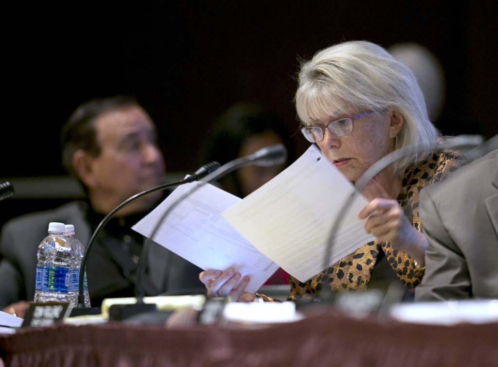 Lynn Schenk, a member of the California High-Speed Rail Authority, looks over papers at a rail board hearing Tuesday, Sept. 19, 2017, in Sacramento, Calif. Schenk and fellow board member Ernest Camacho, left, were critical of the budget overruns in the construction of the first leg of the rail system.