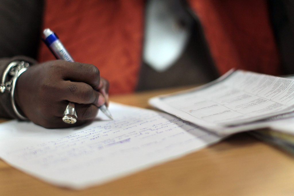 A woman writes a hand-written cover letter at a career training center operated by the New York Department of Labor in Harlem on December 3, 2010 in New York City.