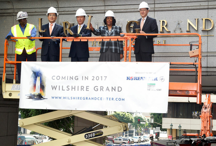 City officials remove the Wilshire Grand Hotel lettering at the Wilshire Boulevard entrance on Tuesday, in celebration of the start of demolition to make way for the new Wilshire Grand Center.