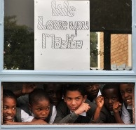 School children stand under a drawing on Jan. 27, 2011 in the vicinity of Milpark Hospital in Johannesburg, South Africa where former President Nelson Mandela was admitted for routine tests.