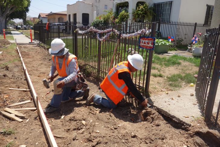 Two workers with Torres Construction set forms for new sidewalks to be poured.