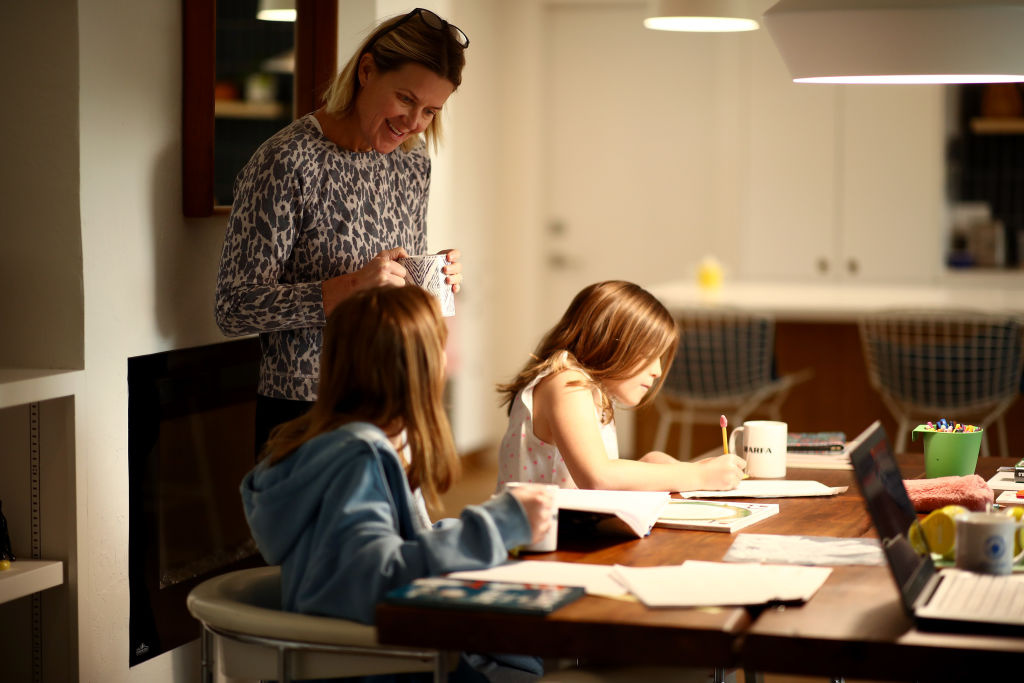 Daisley Kramer helps her daughters, sixth grader Frances and fourth grader Lucy, with schoolwork at home on March 18, 2020 in San Anselmo, California.
