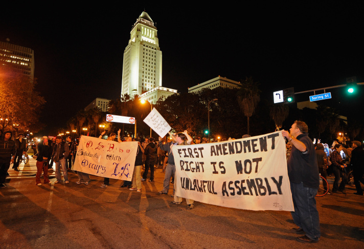 Occupy LA protesters demonstrate on the front lawn of Los Angeles City Hall after the midnight deadline set by city officials to shut down the encampment expired on November 28, 2011 in Los Angeles, California. Los Angeles Mayor Antonio Villaraigosa on Friday gave the protesters outside City Hall until 12:01 am Monday to dismantle their campsite and leave. This morning, although some arrests were made, police have not yet cleared the camp.