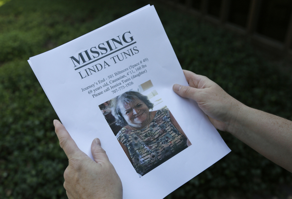 Jessica Tunis stands outside a Red Cross evacuation center and holds a flyer about her missing mother Wednesday, Oct. 11, 2017, in Santa Rosa, Calif. Tunis was searching for her missing mother, Linda Tunis, who was later confirmed dead after a fire consumed her mobile home.