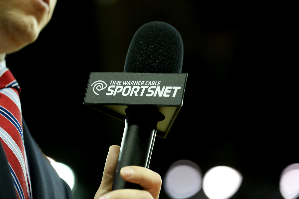 A sideline reporter holds a microphone with the logo of Time Warner Cable Sportsnet.