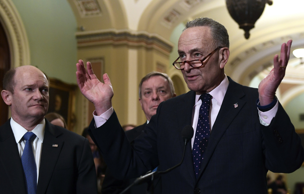 Senate Minority Leader Sen. Chuck Schumer of N.Y., right, responds to a reporter's question on Capitol Hill in Washington, Tuesday, Feb. 13, 2018, following the weekly Democratic policy luncheon.