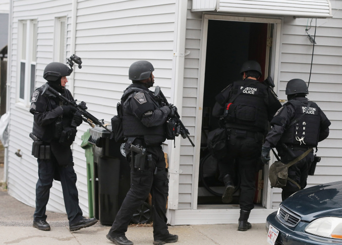 Two police officers laugh while securing the area around Franklin Street on April 19, 2013 in Watertown, Massachusetts.