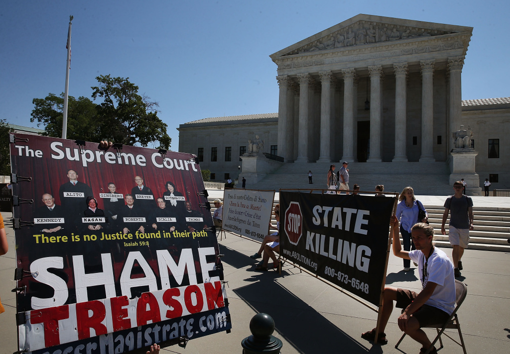 Protesters with signs gather outside of the U.S. Supreme Court June 29, 2015 in Washington, DC. Today the high court ruled on the controversial drug that was implicated in botched executions, state efforts to reduce partisan influence in congressional redistricting and Environmental Protection Agency limits on the emission of mercury and other toxic pollutants from power plants.