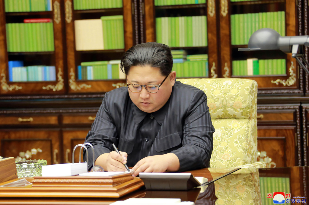 This photo taken on November 28, 2017 and released on November 29, 2017 by North Korea's official Korean Central News Agency (KCNA) shows North Korean leader Kim Jong-Un signing an order document of a test-fire of the inter-continental ballistic rocket Hwasong-15.