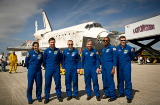 In this handout image provided by NASA, NASA Astronauts and STS-133 mission crew members, from left, Mission Specialists Nicole Stott, Michael Barratt, Pilot Eric Boe, Commander Steve Lindsey, Mission Specialists Alvin Drew, and Steve Bowen pose for a photograph in front of the space shuttle Discovery after they landed at Kennedy Space Center after returning for the last time from a space flight to the International Space Station on March 9, 2011 in Cape Canaveral, Florida.
