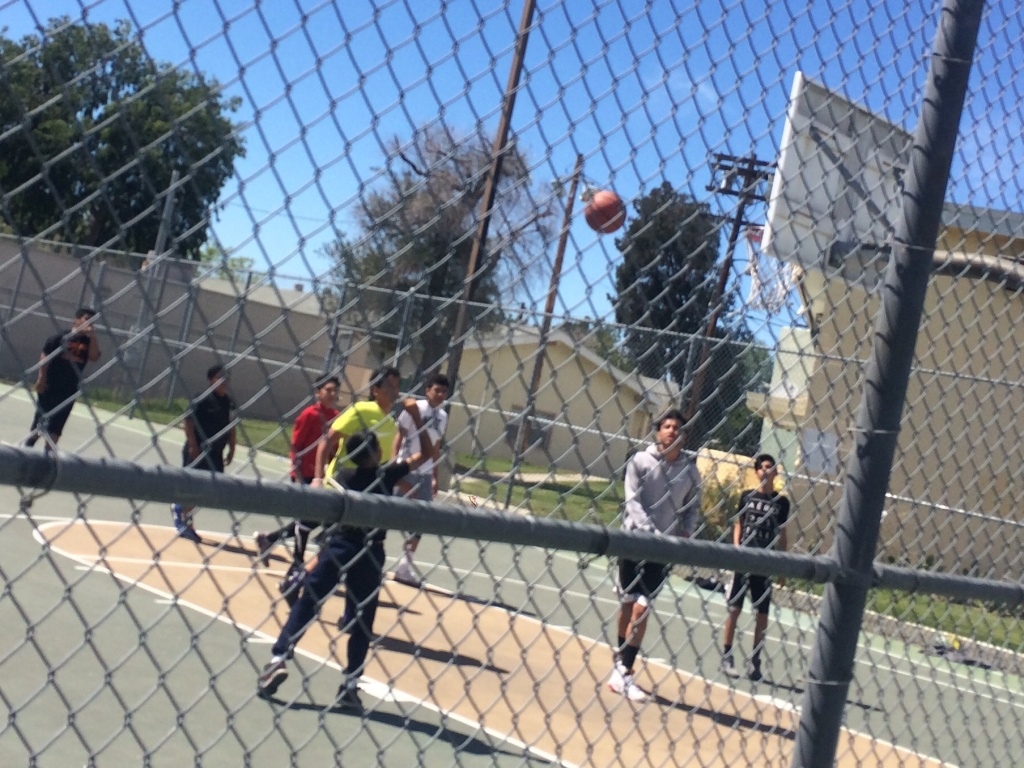 Children and teens play basketball at San Fernando Gardens housing in Pacoima in March, 2016. Just four months earlier, a 15-year-old was shot and killed on the block, an incident local police called gang-related.