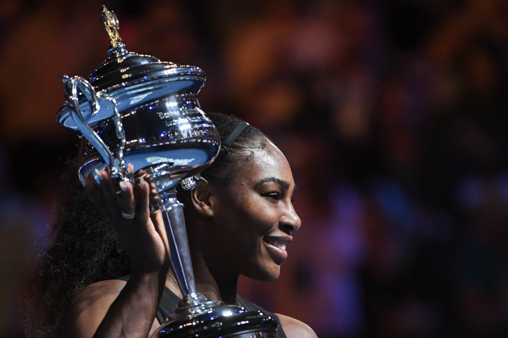 Serena Williams of the US celebrates with the championship trophy after her victory against her sister Venus in the women's singles final on day 13 of the Australian Open on January 28, 2017.