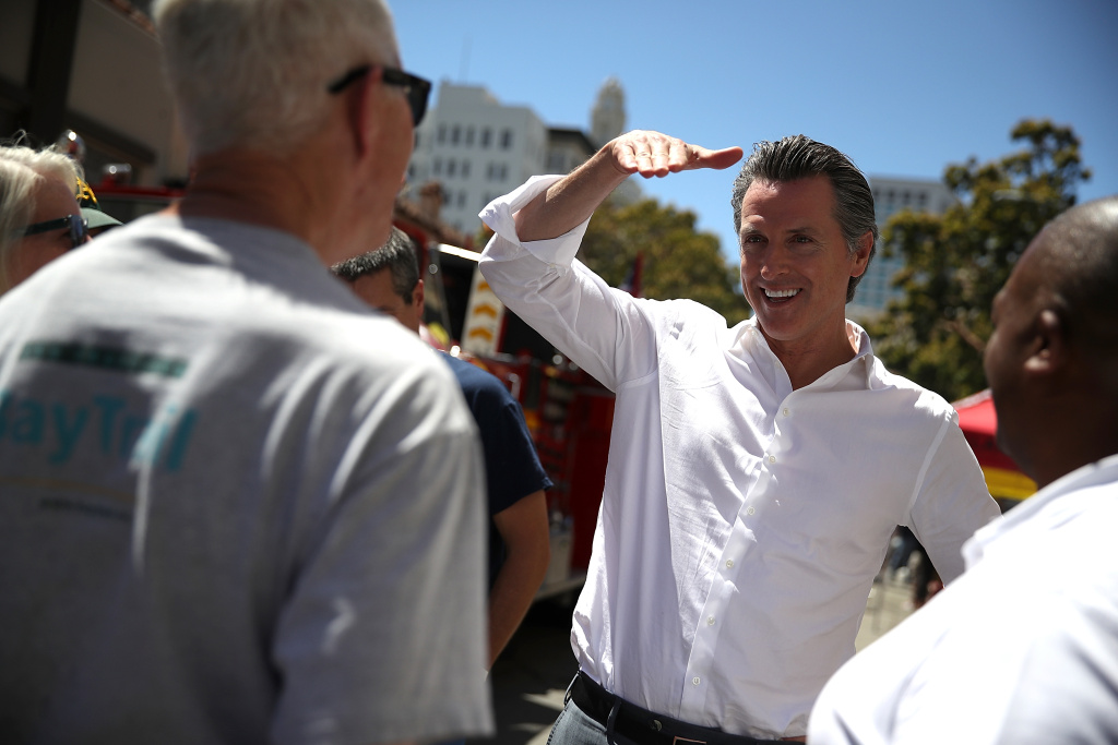 OAKLAND, CA - JUNE 02:  California Lt. Gov. and democratic candidate for California governor Gavin Newsom (C) greets supporters during a campaign stop at California Assemblyman Rob Bonta's Chili Cook Off on June 2, 2018 in Oakland, California.  With less than a week to go until the California primary, Gavin Newsom is campaigning throughout the state.  (Photo by Justin Sullivan/Getty Images)