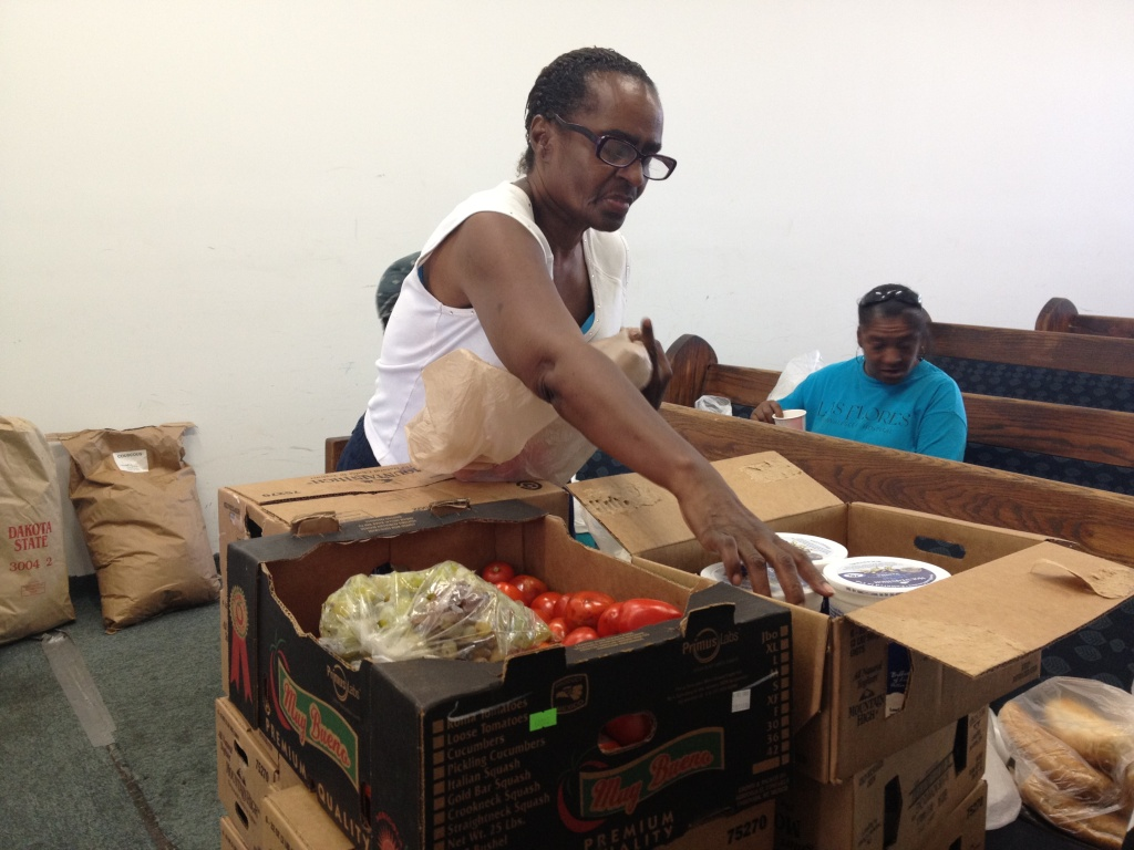 Dolores Taylor a church member of the House of Praise, fills plastics bags with vegetables and packaged food for people who come in Thursday afternoons for the church's food bank distribution.