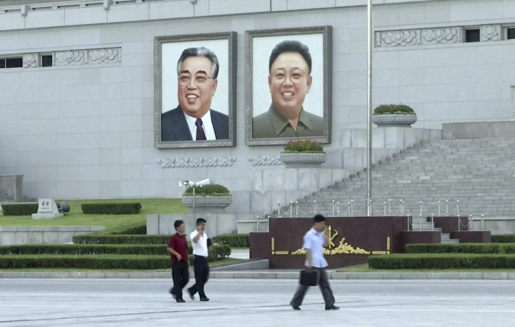 In this image made from video, pedestrians walk beneath portraits of Kim Il Sung, left, and Kim Jong Il, at Kim Il Sung square in Pyongyang, North Korea, on Friday, Aug. 11, 2017.