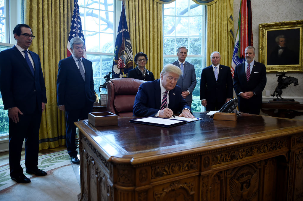 US President Donald Trump signs the Paycheck Protection Program and Health Care Enhancement Act in the Oval Office of the White House in Washington, DC, on April 24, 2020.