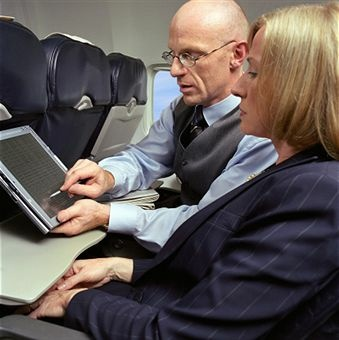 File photo of passengers using a tablet on an airplane.