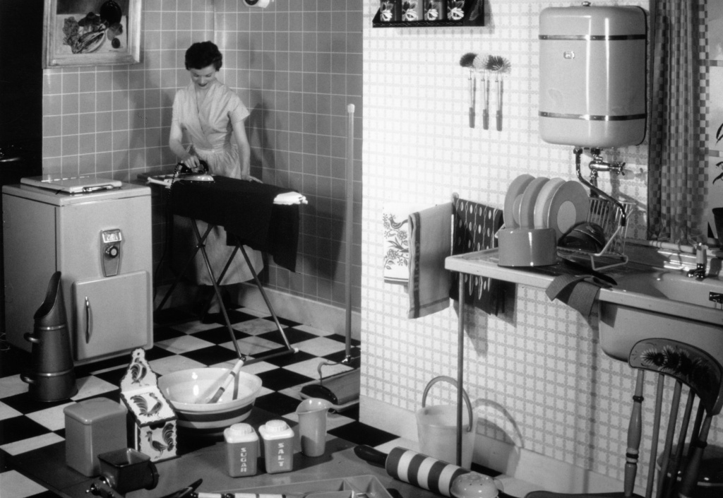 A woman ironing in her kitchen. New research shows that the household chore gender gap is slowly shrinking.