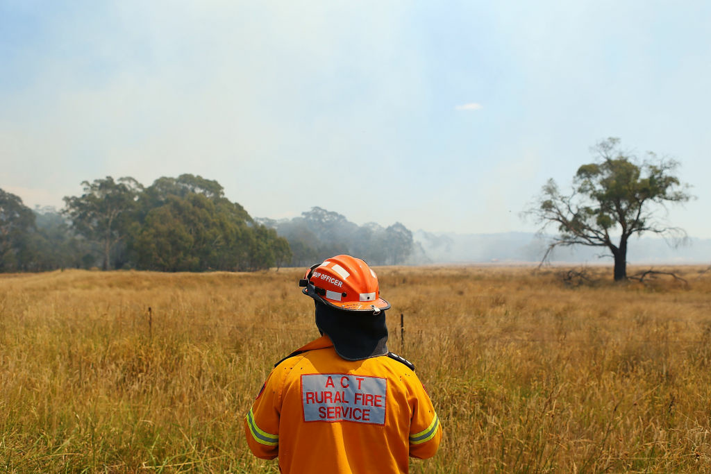 A ACT Rural Fire Service member watches water-bombing operations take place on a fire at Sandhills on January 9, 2013 in Bungendore, Australia. Temperatures cooled overnight offering relief to fire fighters following yesterday's heat wave recording temperatures of over 40-plus degrees across the state. Crews continue to fight blazes today, taking advantage of the improved conditions ahead fire danger conditions predicted later in the week.